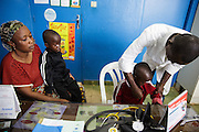 Katy Cherif, 40, and her twin sons Lacine (right) and Lusseini, both 4 and suffering from malaria and diarrhea, meet with a nurse at the Libreville health center in Man, Cote d'Ivoire on Wednesday July 24, 2013.