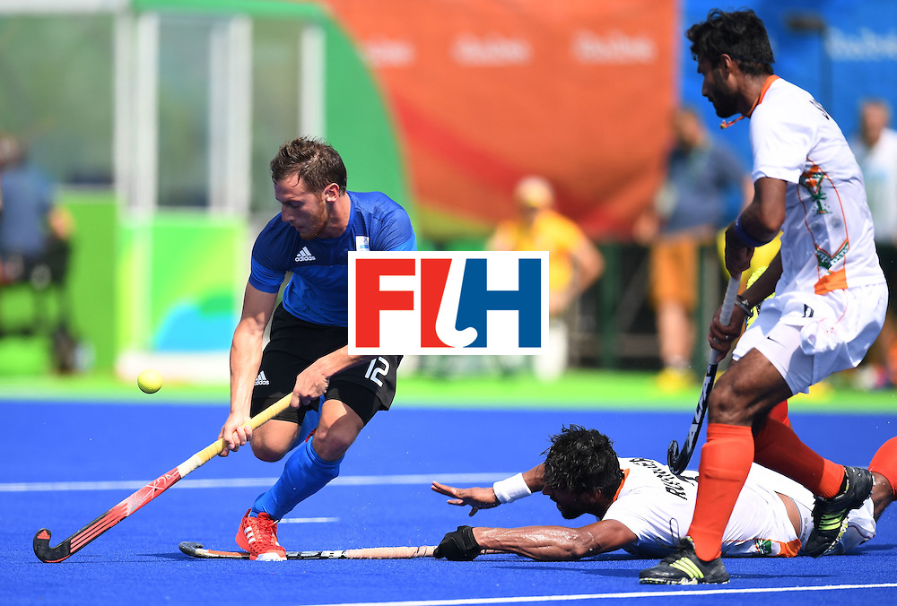 Argentina's Lucas Vila gets past India's Surender Kumar (R) and Rupinder Pal Singh during the men's field hockey Argentina vs India match of the Rio 2016 Olympics Games at the Olympic Hockey Centre in Rio de Janeiro on August, 9 2016. / AFP / MANAN VATSYAYANA        (Photo credit should read MANAN VATSYAYANA/AFP/Getty Images)