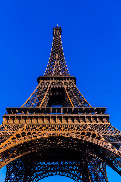 View of the Eiffel Tower from Champ de Mars Park. It is the world famous wrought-iron lattice tower that is the most famous landmark of Paris, France.
