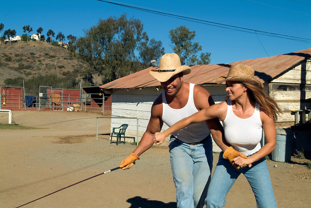 Lifestyle image of young couple horsing around at ranch in San Diego, CA.