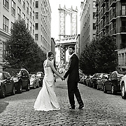 Black & White photo of Bride and Groom walking down cobblestone Brooklyn NY street with Manhattan Bridge in background