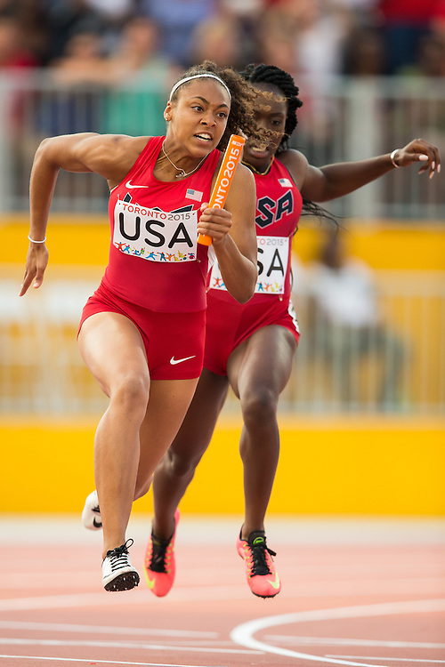Kaylin Whitney (L) of the United States takes the baton from teammate Morolake Akinosun in the women's 4X100 metres at the 2015 Pan American Games at CIBC Athletics Stadium in Toronto, Canada, July 25,  2015.  AFP PHOTO/GEOFF ROBINS