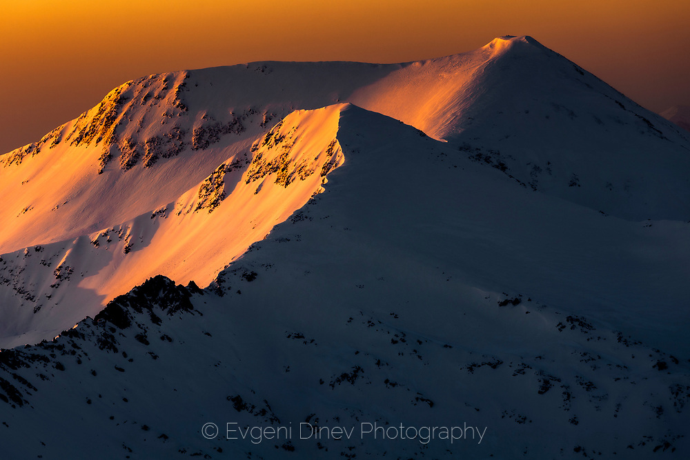 Mountain peaks covered with snow in winter time at sunrise