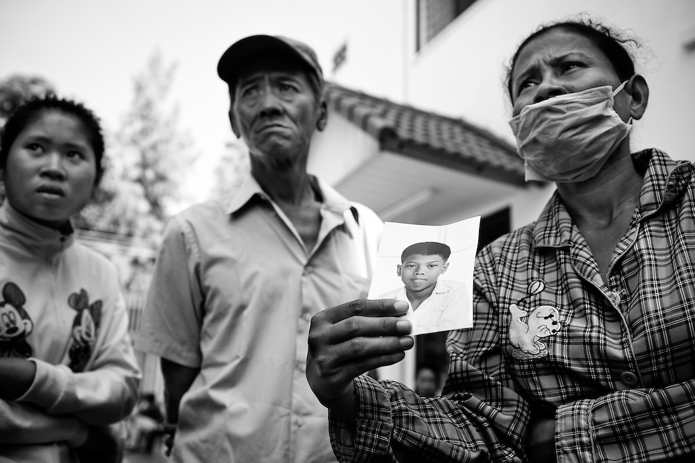 A husband and wife show the photo of their still missing fourteen year old son at Calmette Hospital in Phnom Penh, Cambodia. A young man was still unidentified here, but it wasn't their son.