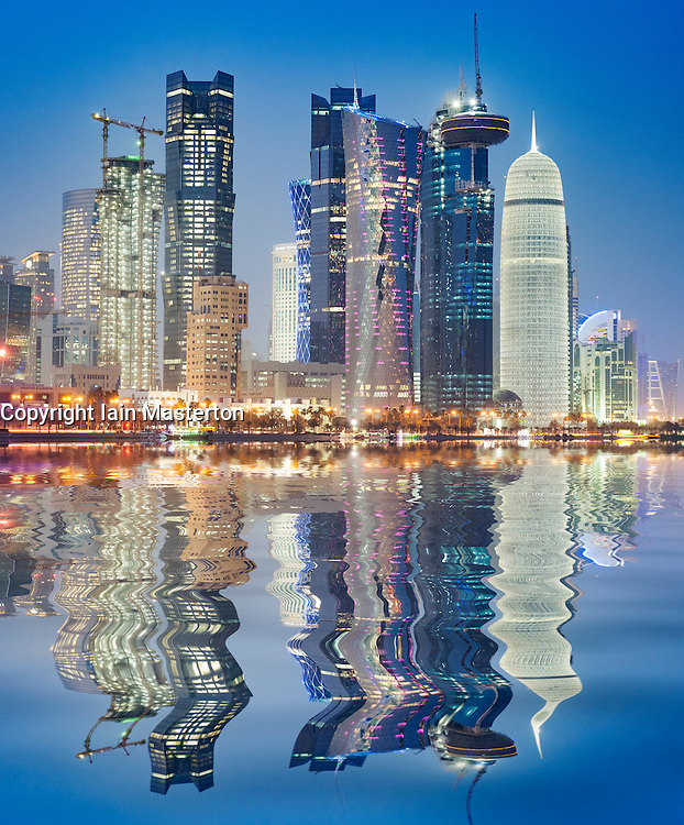 Night view of skyline along waterfront of Corniche towards modern office towers in West Bay district of Doha Qatar