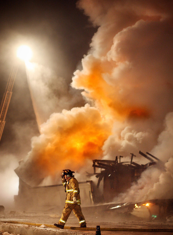 JEROME A. POLLOS/Press..A firefighter leaves the front line of a fire as a ladder truck douses the flames at the 7-11 convenience store at 4th Street and Best Avenue early Saturday. The fire took firefighters nearly two hours to extinguish and destroyed the building.