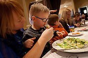 Carter Davidson, center, is fed a piece of lettuce by CobiLynn Dickinson, left, a fellow mother with a child on the autism spectrum during lunch at BRIO Tuscan Grill in Murray, Friday, Nov. 9, 2012.