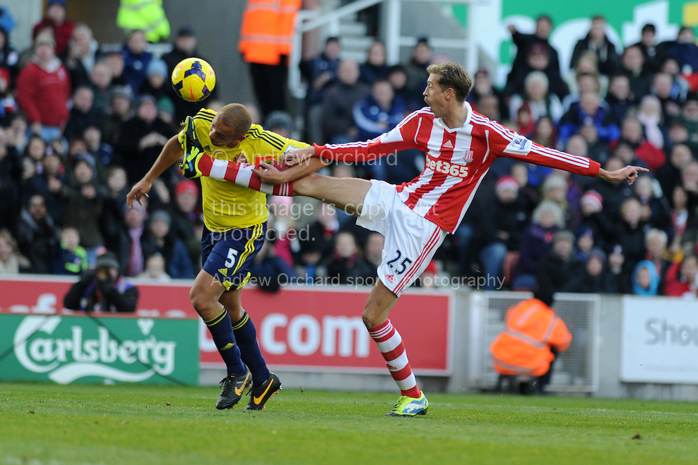 Stoke's Peter Crouch ® challenges Sunderland's Wes Brown. Barclays Premier league, Stoke city v Sunderland at the Britannia stadium in Stoke on Trent, England on Saturday 23rd Nov 2013. pic by Andrew Orchard, Andrew Orchard sports photography,