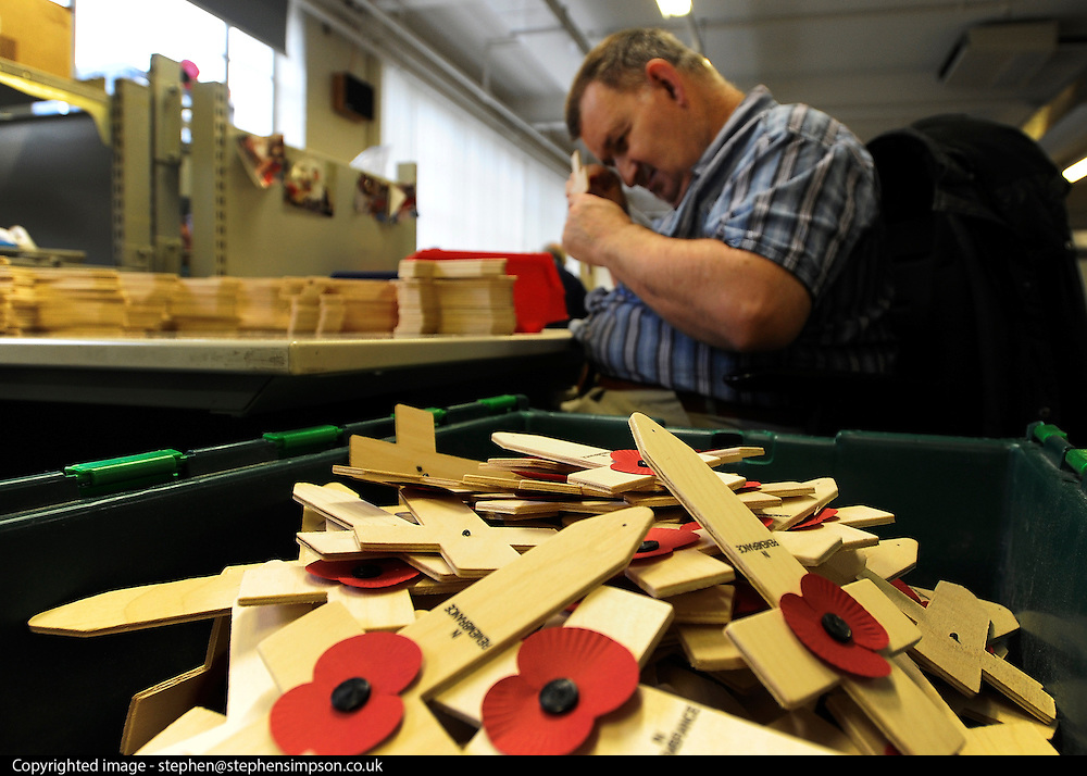© Licensed to London News Pictures. 07/11/2011. Richmond, UK. A worker assembles crosses. Red Poppies being made in The Poppy Factory in preparation for sale in 2012, Richmond, Surrey today 7th November.  The factory has been supplying the poppy, crosses and wreathes to the British Legion for almost 90 years. It is staffed by veterans, many whom of which are injured, sick or wounded of all ages. Photo credit : Stephen Simpson/LNP
