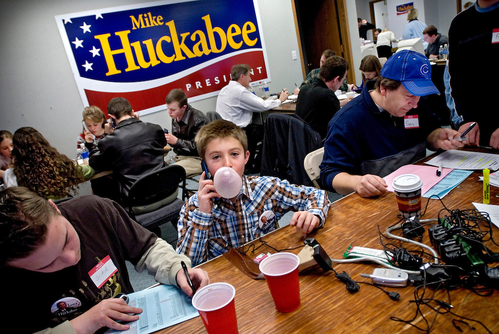 Iowa Caucus.Weston Smith, (with bubble gum)  is part of a group of 21 adults and children, all home-schoolers, who traveled from Flagstaff to volunteer for Huckabee's Iowa campaign. The children, many of them grade school age, have been helping to staff Huckabee's daily phone bank operation...Here they are at the Huckabee campaign headquarters in downtown Des moines, doing last-minute phonecalls to potential voters to get them to caucus for Huckabee...Photo by Chris Maluszynski /MOMENT