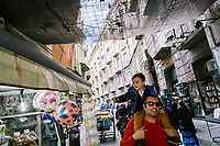 """NAPLES, ITALY - 24 NOVEMBER 2018: Father and son are seen here by Port'Alba arch  in Naples, Italy, on November 24th 2018.<br /> <br /> My Brilliant Friend (Italian: L'amica geniale) is an Italian-American drama television miniseries based on the novel of the same name by Elena Ferrante. The series follows the lives of two perceptive and intelligent girls, Elena (sometimes called """"Lenù"""") Greco and Raffaella (""""Lila"""") Cerullo, from childhood to adulthood and old age, as they try to create lives for themselves amidst the violent and stultifying culture of their home – a poor neighborhood on the outskirts of Naples, Italy. My Brilliant Friend is a co-production between American premium cable network HBO and Italian networks RAI and TIMvision"""
