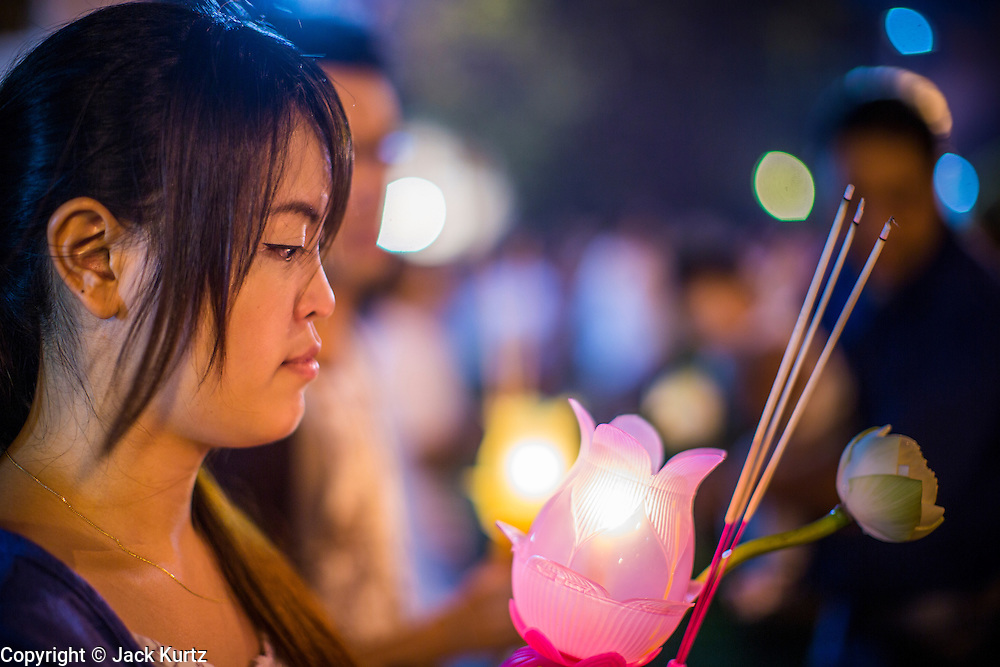 """25 FEBRUARY 2013 - BANGKOK, THAILAND:   A woman with a lantern joins a procession around Wat Benchamabophit Dusitvanaram (popularly known as either Wat Bencha or the Marble Temple) on Makha Bucha Day. Thais visit temples throughout the Kingdom on Makha Bucha Day to make merit and participate in candle light processions around the temples. Makha Bucha is a Buddhist holiday celebrated in Myanmar (Burma), Thailand, Cambodia and Laos on the full moon day of the third lunar month (February 25 in 2013). The third lunar month is known in Thai is Makha. Bucha is a Thai word meaning """"to venerate"""" or """"to honor"""". Makha Bucha Day is for the veneration of Buddha and his teachings on the full moon day of the third lunar month. Makha Bucha Day marks the day that 1,250 Arahata spontaneously came to see the Buddha. The Buddha in turn laid down the principles his teachings. In Thailand, this teaching has been dubbed the 'Heart of Buddhism'.    PHOTO BY JACK KURTZ"""