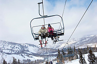 Teenage couple (16-19) wearing skis sitting on ski lift low angle view.
