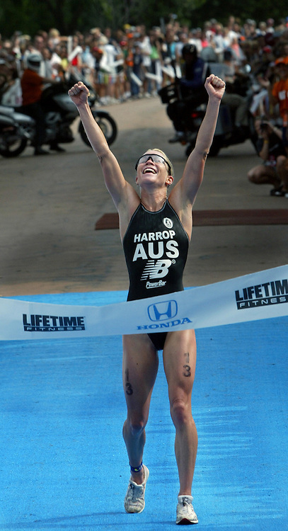 The winner of a triathlon in Minneapolis, MN celebrates her victory at the finish line.