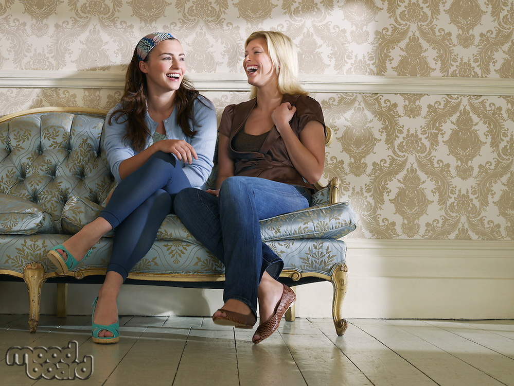 Two young women sitting on sofa laughing
