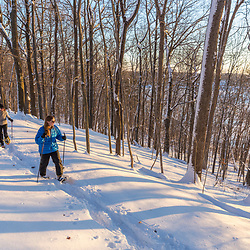 Three women snowshoeing through the forest above Indian Hill Reservoir in West Newbury, Massachusetts.