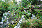 Woman and two children on bridge and walkway over waterfall, Krka National Park, Croatia