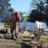 Butch Skelton of Cottondale, Alabama raises the lid of a Dutch oven full of biscuits at the Civil War encampment on the lawn of The Magnolias.
