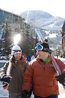 A couple of skiers laugh with each other as they walk through Whistler Village on a sunny winter day.