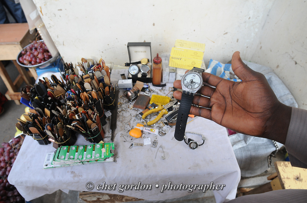 A Nigerian watch repairman displays a watch at his stand at the Wuse Market in Abuja, Nigeria on Saturday, December 8, 2012.