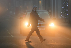 © Licensed to London News Pictures. 22/12/2016. London, UK. A man crosses Ealing Broadway in thick fog on a cold winter morning. Temperatures over the upcoming Christmas period are expected to be unusually warm. Photo credit: Ben Cawthra/LNP
