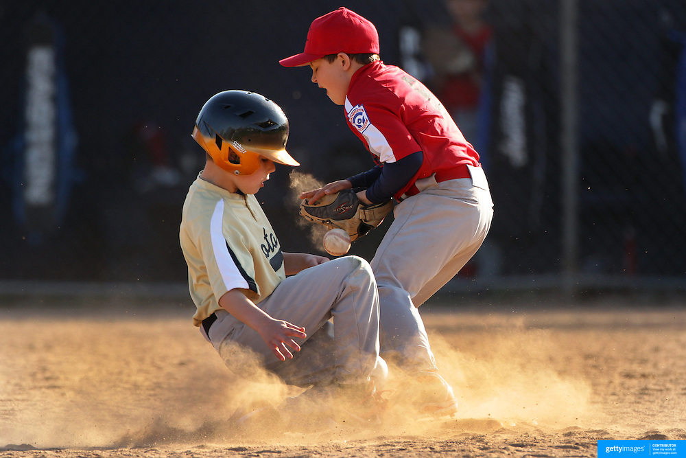 A young baseball player slides into second base during the Norwalk Little League baseball competition at Broad River Fields,  Norwalk, Connecticut. USA. Photo Tim Clayton