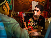 17 FEBRUARY 2016 - BANGKOK, THAILAND: Men in a small opera troupe chat while putting on their makeup before a performance in Bangkok. The small troupe travels from Chinese shrine to Chinese shrine performing for a few nights before going to another shrine. They spend about half the year touring in Thailand and the other half of the year touring in Malaysia. Members of the troupe are paid about 5,000 Thai Baht per month (about $140 US). Chinese opera was once very popular in Thailand, where it is called Ngiew. It is usually performed in the Teochew language. Millions of Chinese emigrated to Thailand (then Siam) in the 18th and 19th centuries and brought their culture with them. Recently the popularity of ngiew has faded as people turn to performances of opera on DVD or movies. There are still as many 30 Chinese opera troupes left in Bangkok and its environs. They are especially busy during Chinese New Year and Chinese holiday when they travel from Chinese temple to Chinese temple performing on stages they put up in streets near the temple, sometimes sleeping on hammocks they sling under their stage. Most of the Chinese operas from Bangkok travel to Malaysia for Ghost Month, leaving just a few to perform in Bangkok.     PHOTO BY JACK KURTZ