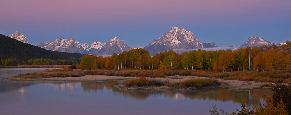 Dawn casts a purple glow over Mount Moran and the Teton Range as seen from the Oxbow Bend of the Snake River.