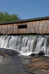 Water falls past the Watson Mill Bridge in the Watson Mill Bridge State Park near Carlton, Georgia.  The park is home to the longest original-site covered bridge in Georgia, which spans 229 feet across the South Fork River. The bridge, being more than 100 years old, is supported by a town lattice truss system held firmly together with wooden pins.