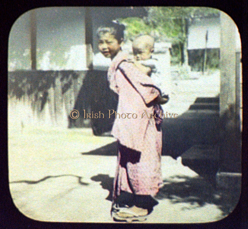 Young Japanese mother carrying her baby on her back. Hand-coloured magic lantern slide, 1895.