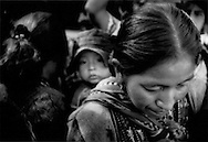 Indigenous woman, child on her back, navigates through a weekly market in the highland village of Solala, Guatemala.
