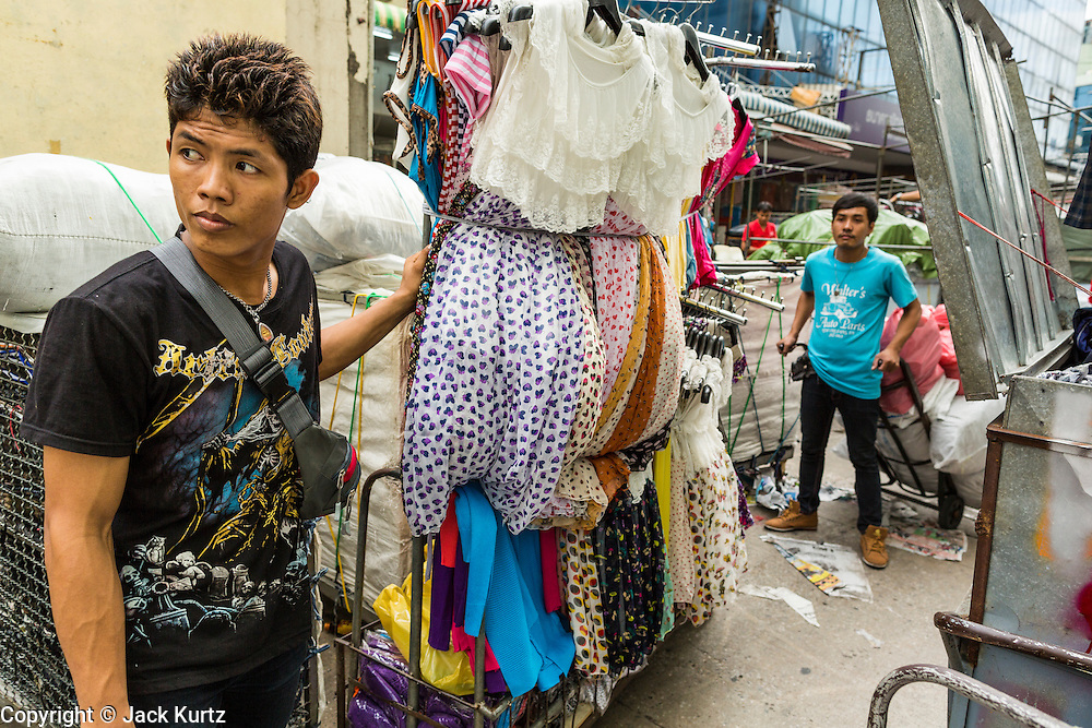 06 JUNE 2013 - BANGKOK, THAILAND:     A vendor rolls his inventory through Bobae Market in Bangkok. Bobae Market is a 30 year old market famous for fashion wholesale and is now very popular with exporters from around the world. Bobae Tower is next to the market and  advertises itself as having 1,300 stalls under one roof and claims to be the largest garment wholesale center in Thailand.       PHOTO BY JACK KURTZ