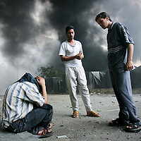 An Iraqi man weeps, left, as others look on following a large blast outside of the Agriculture Ministry and a hotel used by Western contractors in Baghdad, Iraq. A suicide bomber detonated a garbage truck packed with explosives killing at least three people, officials said. The bomber also died. March 2005.