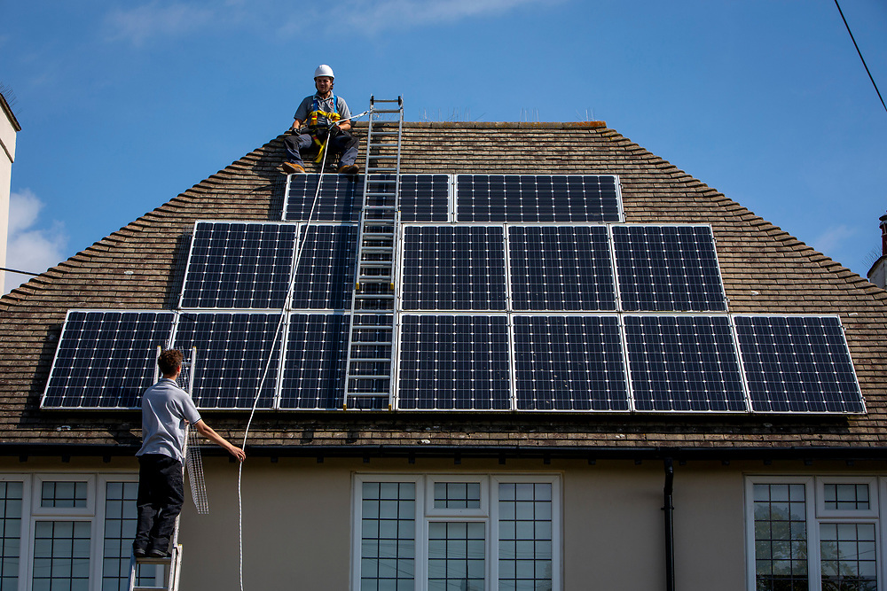A maintenance person uses a ladder to pass equipment to his colleague that will be installed around a Solar panel array on the roof of a house to stop birds nesting underneath. Folkestone, Kent, United Kingdom.   (photo by Andrew Aitchison / In pictures via Getty Images)