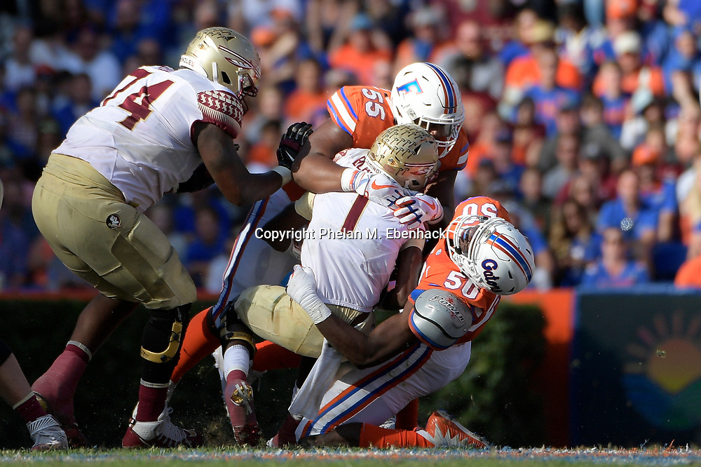 Florida State quarterback James Blackman (1) is sacked by Florida defensive tackle Kyree Campbell (55) and linebacker Jeremiah Moon (50) during the second half of an NCAA college football game Saturday, Nov. 25, 2017, in Gainesville, Fla. FSU won 38-22. (Photo by Phelan M. Ebenhack)