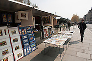 Tourists stroll along the left bank of the Seine River in Paris in front of book and poster vendors.