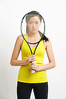 Portrait of young Asian woman holding tennis racket in front of her face against white background