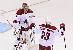 Mar 27, 2014; Newark, NJ, USA; Phoenix Coyotes defenseman Oliver Ekman-Larsson (23) congratulates Phoenix Coyotes goalie Thomas Greiss (1) on his 3-2 shootout win over the New Jersey Devils at Prudential Center.