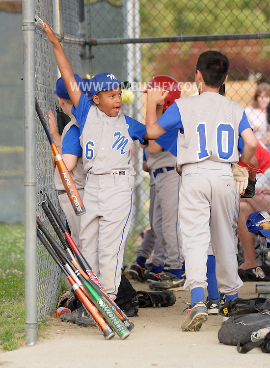Middletown, NY - A baseball player in the dugout gives a high-five to a teammate during a game at Watts Park on July 11, 2008.