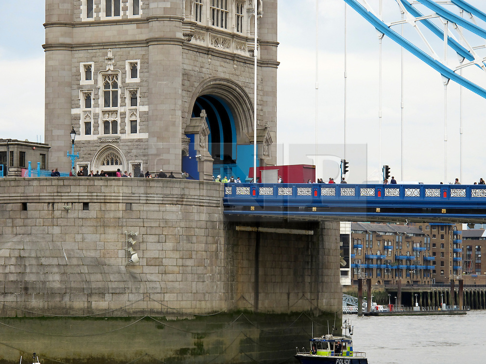 © licensed to London News Pictures. LONDON, UK  13/04/11. A Man threatens to jump from the southern pier of Tower Bridge, London,England on Wednesday 13 April 2011. He was talked to safety by members of the emergency services on at approximately 14.10 hours. A Police helicopter hovered overhead during the incident which lasted no more than 5 - 10 minutes whilst the RNLI rescue boat and Met Police Maritime Unit boat waited underneath the bridge.. Please see special instructions. Photo credit should read Mark Baynes/LNP
