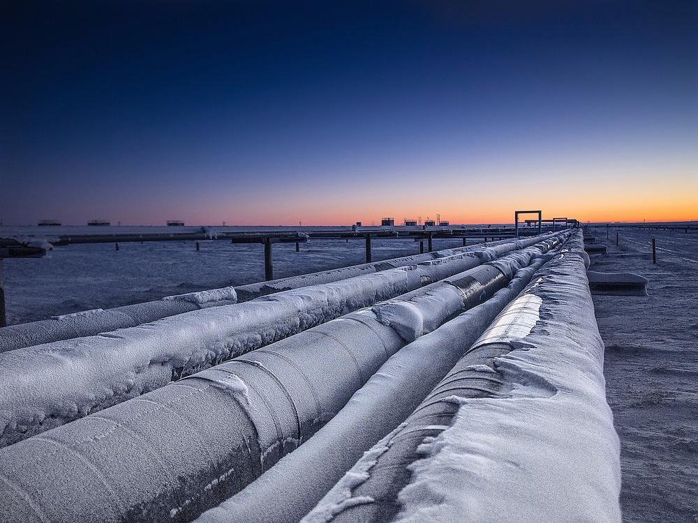 Piplines run towards the setting sun in Prudhoe Bay Alaska.