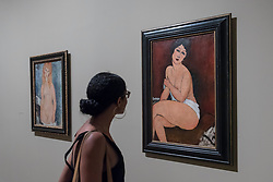 "© Licensed to London News Pictures. 21/11/2017. London, UK.  A visitor views (R) ""Seated Nude (La Belle Romaine)"", 1917.  Preview of ""Modigliani"", the most comprehensive exhibition of works by Amedeo Modigliani ever held in the UK.  On display are iconic portraits, sculptures and 12 nudes, the largest group ever shown in the UK.  The show runs 23 November to 2 April 2018.  Photo credit: Stephen Chung/LNP"