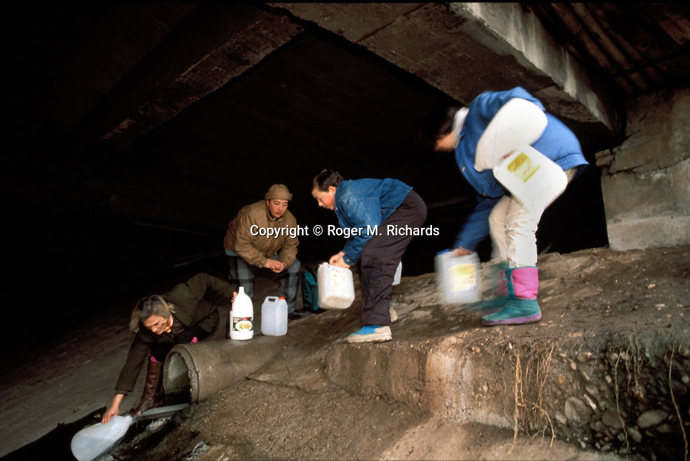"Sarajevo residents use anything they can find to collect water from a stream running under ""Sniper Alley"", 1992. During the siege of the city running water and electricity were scarce, subject to being cut off by the besieging Bosnian Serbs. (Photo by Roger Richards)"