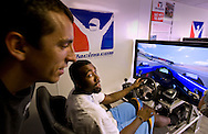 """Kings' Donte Greene, seated and Indy Car's Justin Wilson play on a simulator as Justin gives Donte instructions on the simulator. IndyCar Series driver Justin Wilson, the tallest driver on the series at 6' 3"""", will challenge Sacramento Kings player Donte Greene to a game of """"I-N-D-Y-C-A-R"""" (instead of HORSE) in advance of the Indy Grand Prix of Sonoma at Infineon Raceway, Aug. 21-23. Greene will also battle Wilson at his own game behind the wheel of an IndyCar simulator in the parking lot at Arco Arena. August 19, 2009."""