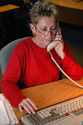 Switchboard operator transferring call to the appropriate department at a busy Hospital,