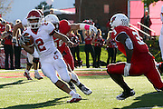 15 October 2011: Dante Warren pressured by Colton Underwood and Evan Frierson during an NCAA football game between the University of South Dakota Coyotes and the Illinois State Redbirds (ISU) at Hancock Stadium in Normal Illinois.