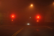 horizontal color photograph of foggy city street with red traffic lights and car headlights at night
