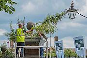 Final preparations are made to the main (London) gate - its wrought iron work is garlanded in flowers.