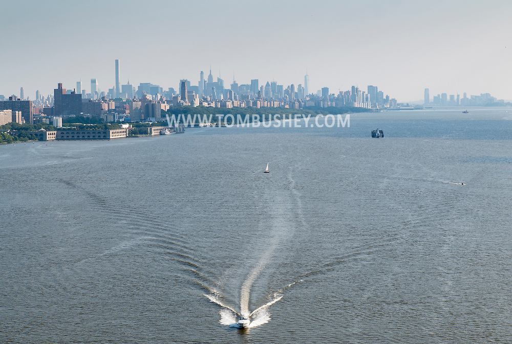 New York, New York - A motor boat speeds north on the Hudson River in a view from the George Washington Bridge on July 11, 2015. The Manhattan skyline is visible in the background.