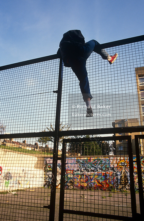 An unidentified youth is seen climbing over a high security fence into a derelict basketball court in the Notting Hill area of West London, England. Half-way over the wire netting, the young man has put his right leg over the top to haul himself over the high barrier. In the distance we see the graffiti left by other kids, sprayed on to the concrete walls of the former sports place. This is an inner-city environment where lawless youth crime is prevalent.